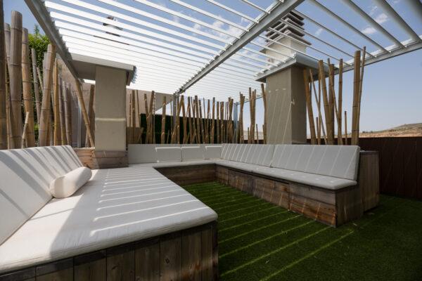 zona de estar terraza madera cesped bambú cojines