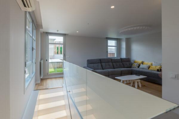 Salón interior con vistas a la terraza escalera acristalada sofá gris